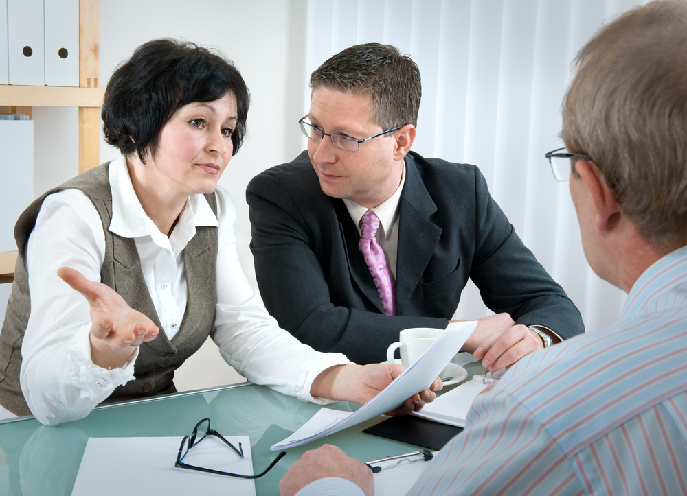 Woman and her lawyer in conversation with husband - Shutterstock